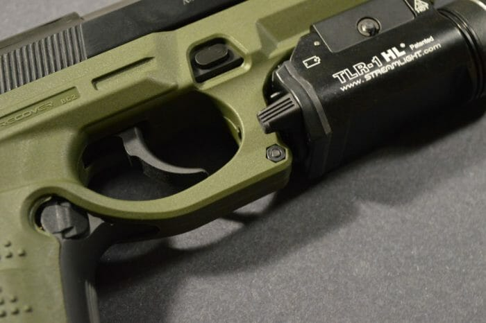 Nuts and bolts such as the one near the front of the trigger guard secure the front of the system.